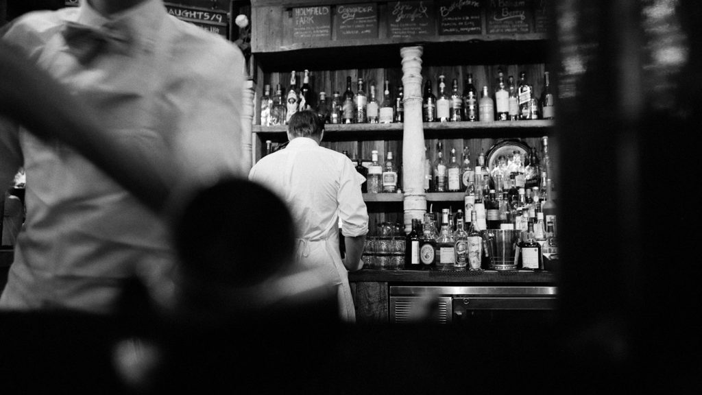 Waitstaff behind bar